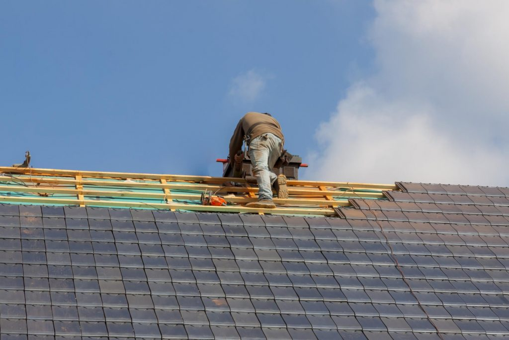 this is an image of our expert roofing contractor installing roof shingles in Encinitas